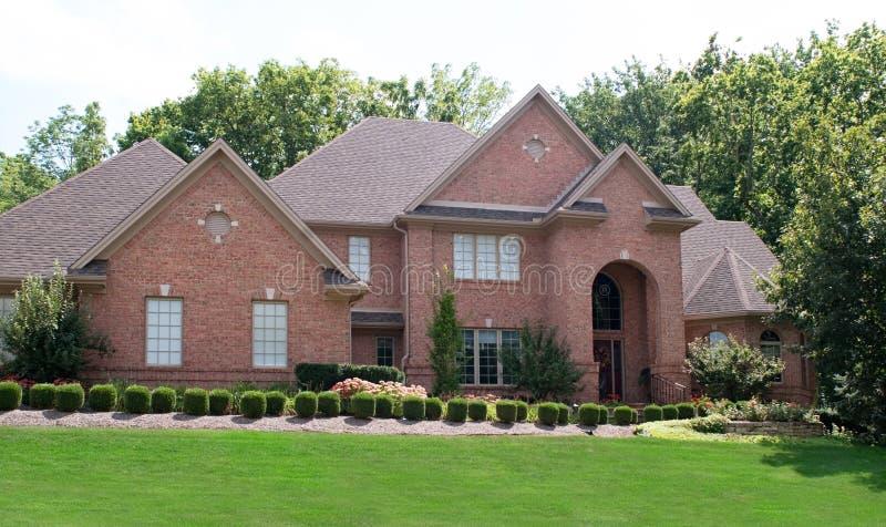 Casa con mattoni a vista rossa con gli arbusti immagine stock libera da diritti