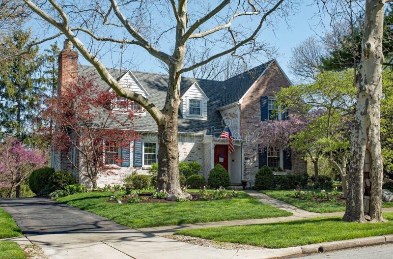 Casa con mattoni a vista stagionata nella regolazione degli alberi di primavera fotografia stock