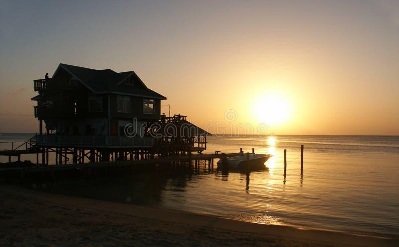 Casa con puesta del sol en la costa imagen de archivo libre de regalías