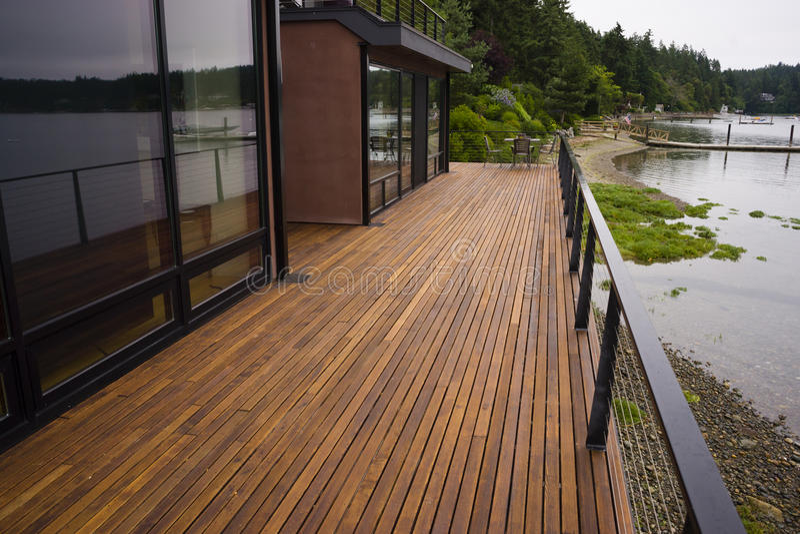 Casa contemporânea da margem da água de madeira da praia do pátio da plataforma da prancha foto de stock