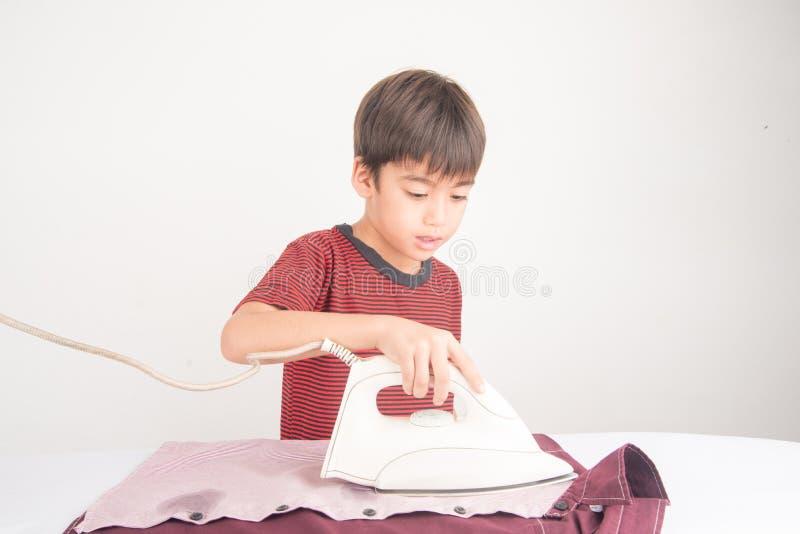 Casa d'aiuto del ragazzino lavorare facendo uso di ferro il suo panno immagini stock
