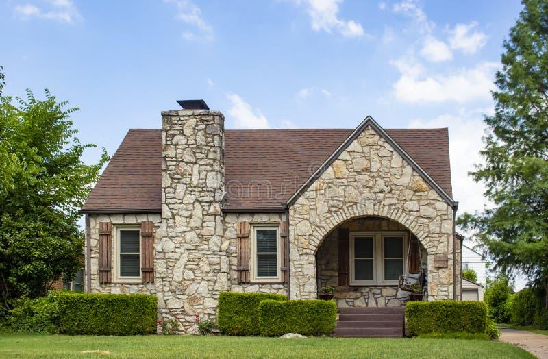 Casa d'annata adorabile della roccia con gli otturatori di legno rustici ed il portico incurvato con appello del bordo dell'oscil immagine stock