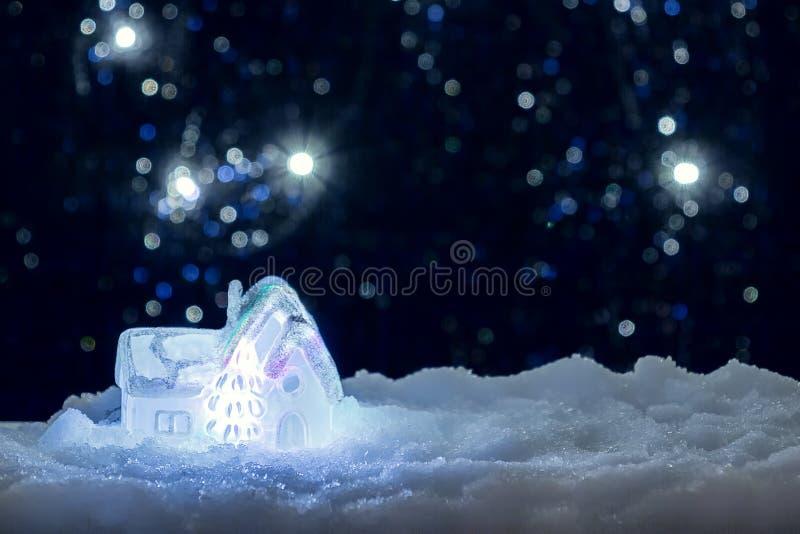 Casa d'ardore del giocattolo nella neve sui precedenti delle luci di Natale Concetto festivo, di Natale o del nuovo anno immagine stock libera da diritti