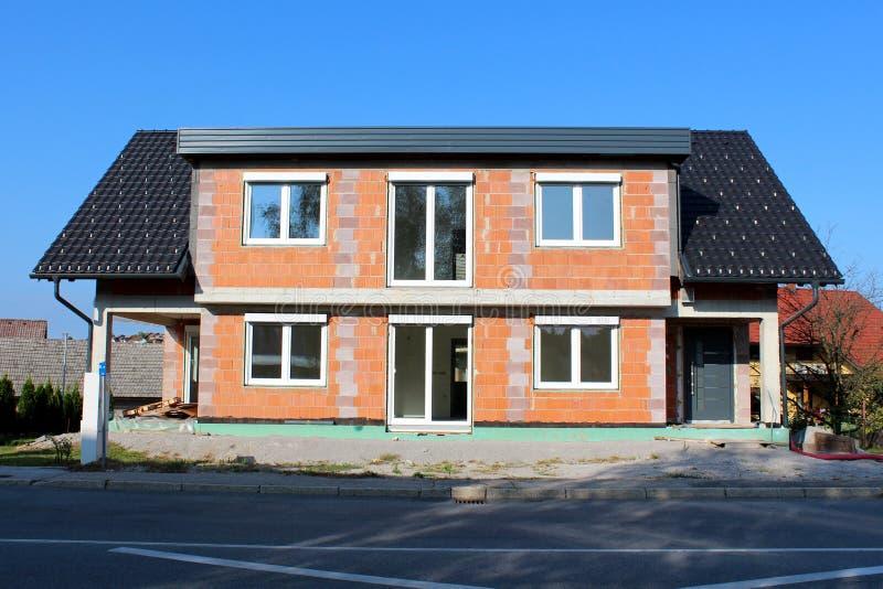 Casa da família sob a construção feita de blocos de apartamentos vermelhos com portas novas e janelas e telhado incomum cercados  foto de stock royalty free