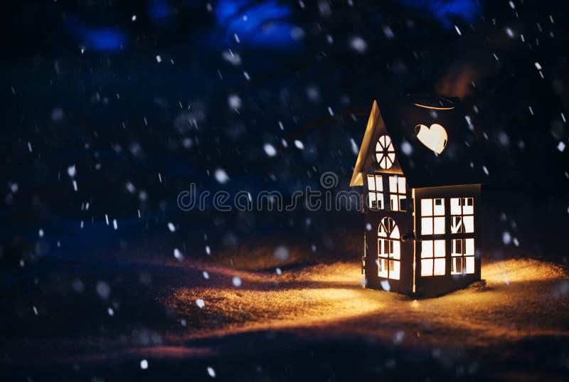 Casa da lanterna com vela ardente na neve na noite foto de stock