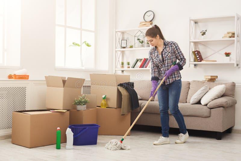 Casa da limpeza da jovem mulher com espanador foto de stock royalty free