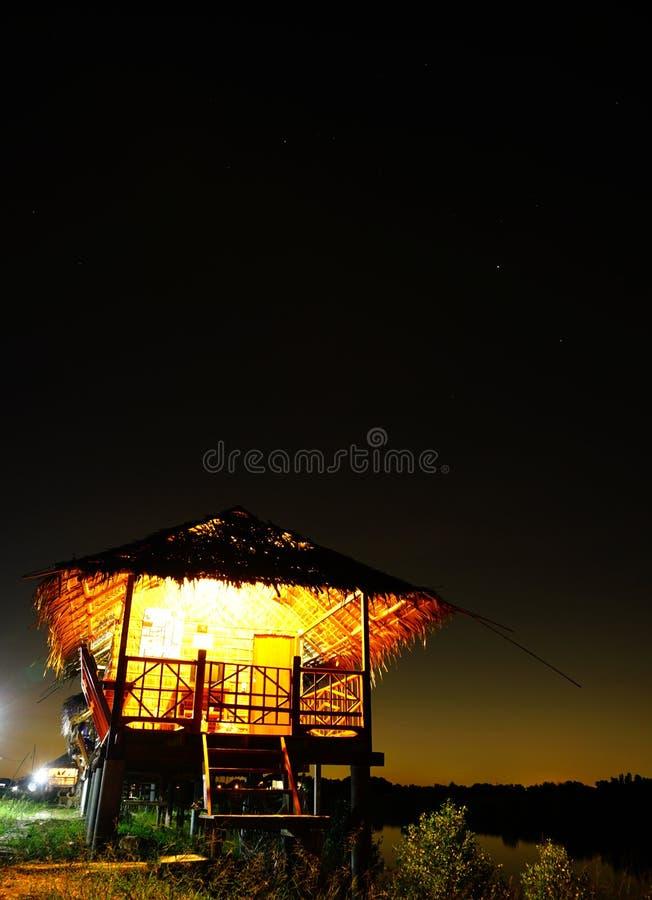 Casa da palha perto do lago pequeno com o céu no nightime fotos de stock royalty free