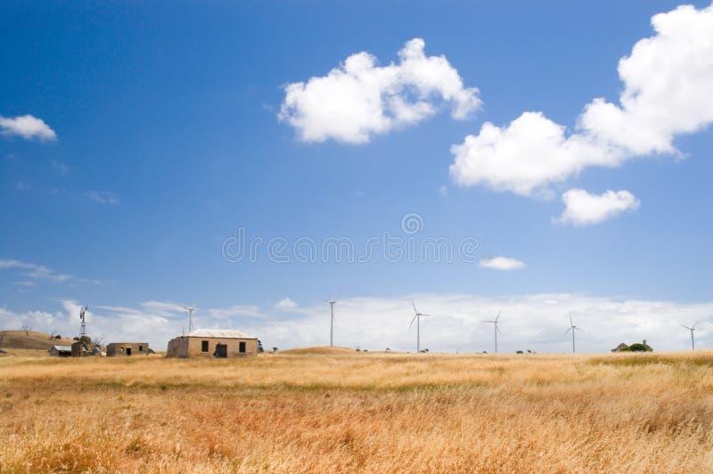 Casa da quinta com contexto das turbinas de vento fotografia de stock royalty free