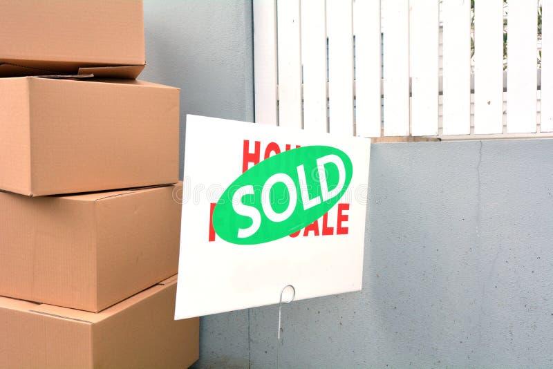 Casa da vendere il segno con l'autoadesivo venduto che lo riguarda immagini stock