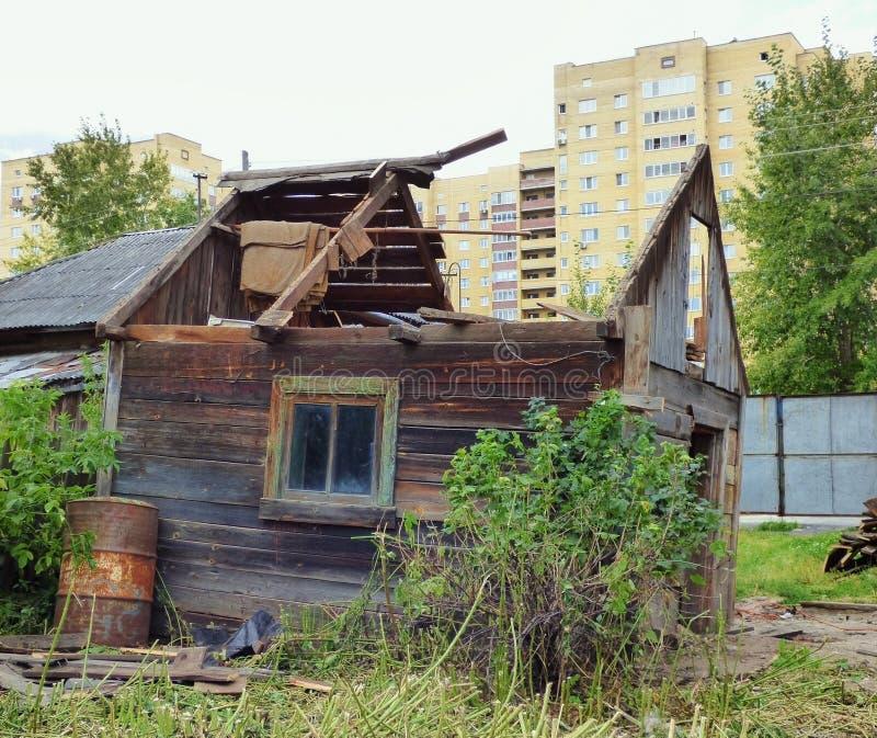 Casa danificada envelhecida pequena contra construções modernas foto de stock