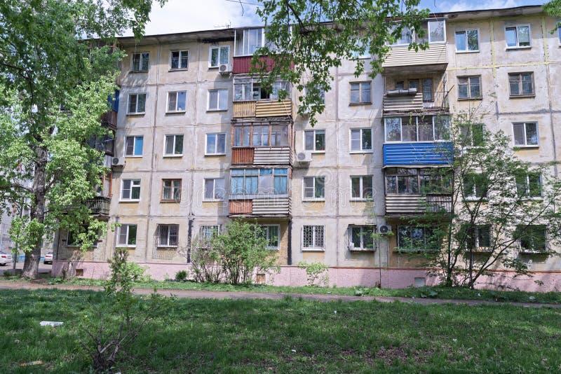 Casa de apartamento velha no prado verde, Komsomolsk-On-Amur, Rússia imagens de stock
