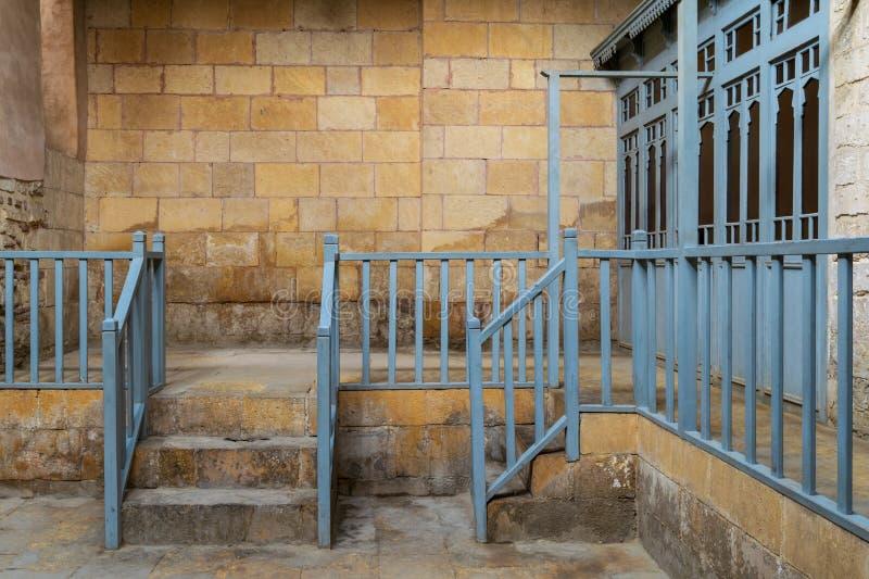 Casa de baños tradicional abandonada con la escalera que lleva a la pared de piedra de los ladrillos, a la barandilla azul de mad fotos de archivo libres de regalías