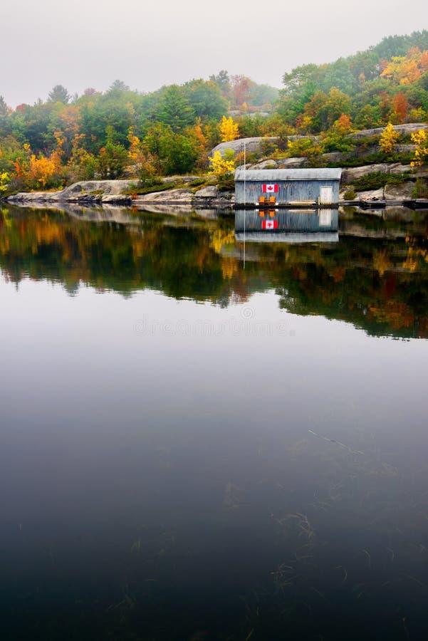 Casa de barco de madeira velha em um lago calmo na queda foto de stock royalty free