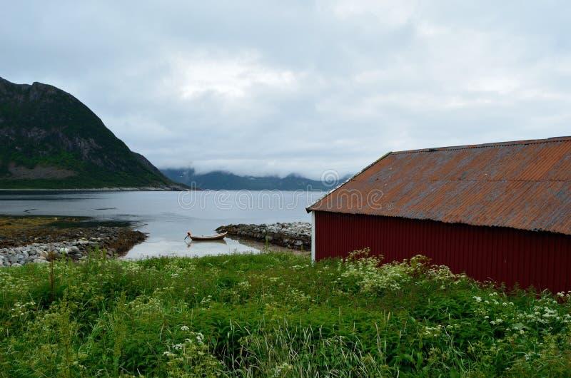 Casa de barco vermelha velha com fundo nebuloso da cordilheira e o barco entrado pequeno imagem de stock royalty free