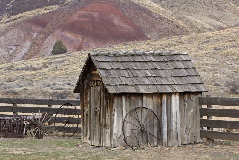 Casa de bomba de madera del vintage con la rueda de carro foto de archivo