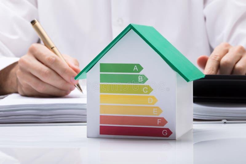 Casa de Calculating Energy Efficient do homem de negócios imagens de stock