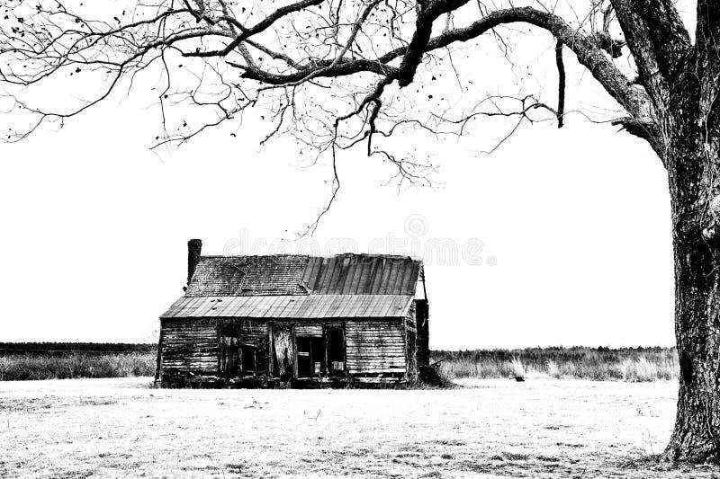 Casa de campo abandonada con roble en frente fotos de archivo