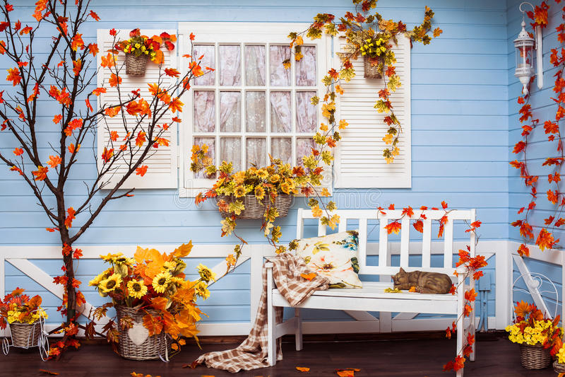 Casa de campo acogedora con las paredes azules y la ventana blanca en otoño imagenes de archivo