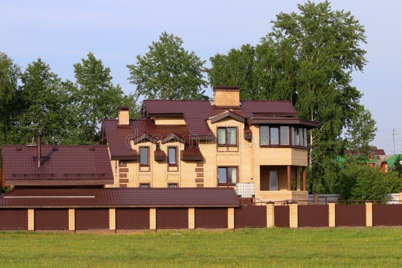 Casa de campo amarela brilhante entre árvores verdes e a cerca marrom imagens de stock royalty free