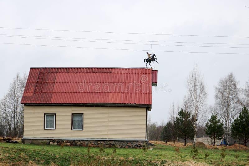 A casa de campo branca aparou com tapume com janelas e um telhado vermelho com uma aleta de tempo sob a forma de um cavaleiro em  foto de stock