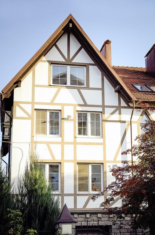 Casa de campo branca com um revestimento bonito com as venezianas de madeira marrons Fotografia vertical fotos de stock royalty free