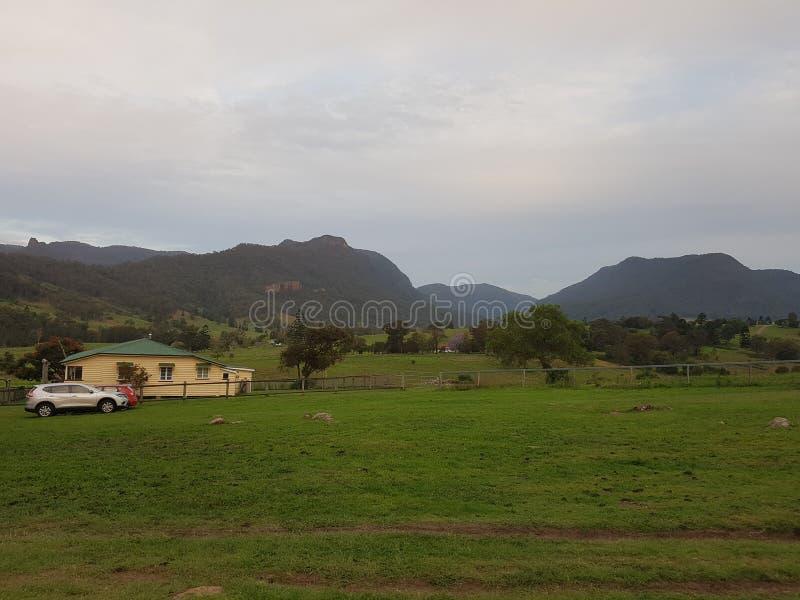 Casa de campo con el coche, las montañas y puesta del sol fotografía de archivo