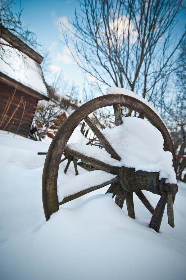 Casa de campo de madeira velha e roda romena de madeira cobertas pela neve Dia de inverno frio no campo Montanhas Carpathian trad imagens de stock royalty free