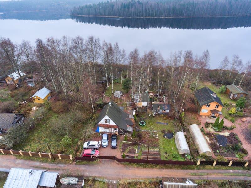 A casa de campo do verão com pátio, celeiros e o jardim pequeno está na costa do lago Vista aérea na estação de mola Rússia fotografia de stock royalty free