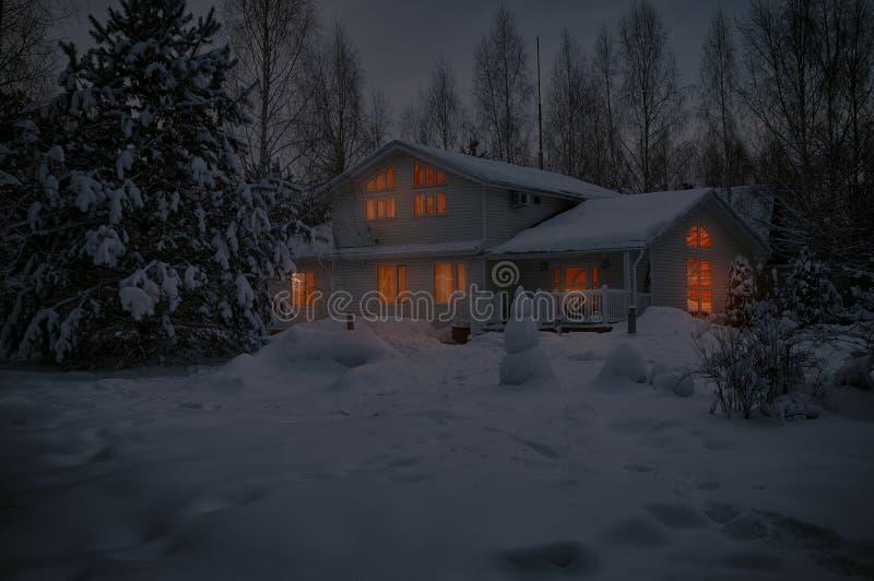 Casa de campo en noche fría nevosa del invierno con las ventanas encendidas el Nochebuena imágenes de archivo libres de regalías