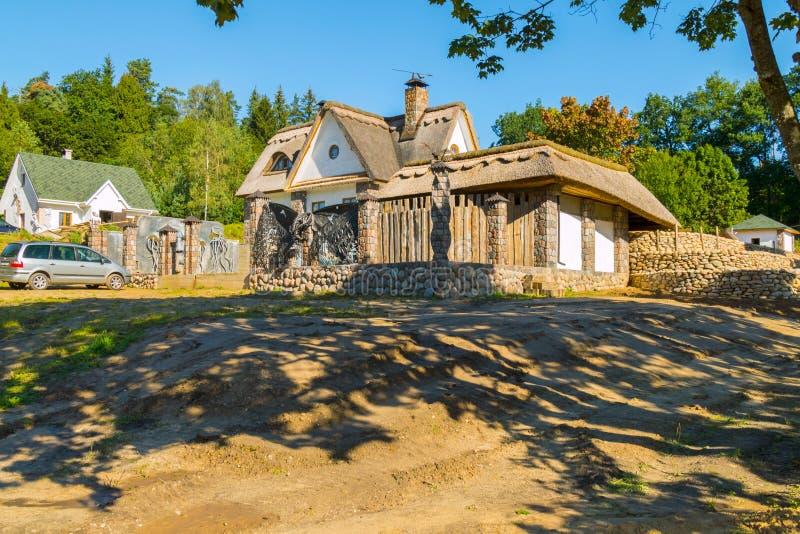 Casa de campo hermosa con la fachada de piedra en un día soleado y claro imagenes de archivo