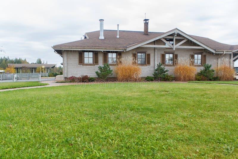 Casa de campo de madeira com projeto verde do gramado e da paisagem fotos de stock