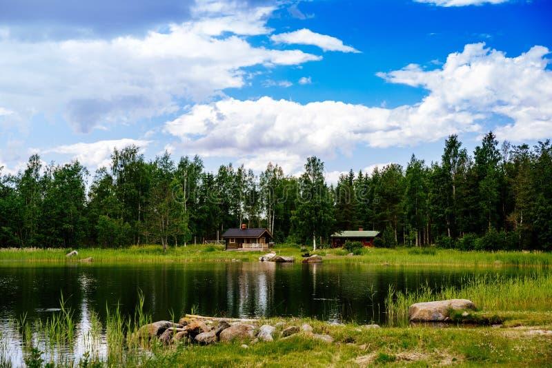 Casa de campo ou cabana rústica de madeira do verão pelo lago azul em Finlandia rural imagens de stock