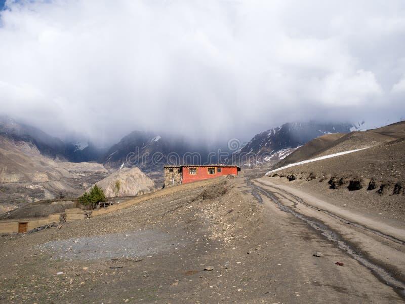 Casa de campo roja con el tiempo del paria en la montaña en la distancia detrás foto de archivo libre de regalías