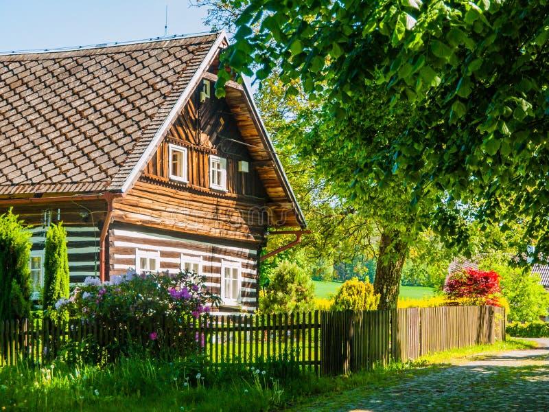 Casa de campo suportada tradicional velha com o jardim verde luxúria romântico e idílico com a cerca de madeira no verão ensolara foto de stock