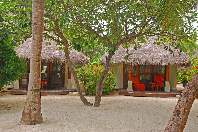 Casa de campo tropical da praia com abundância das árvores na areia fina branca fotografia de stock royalty free