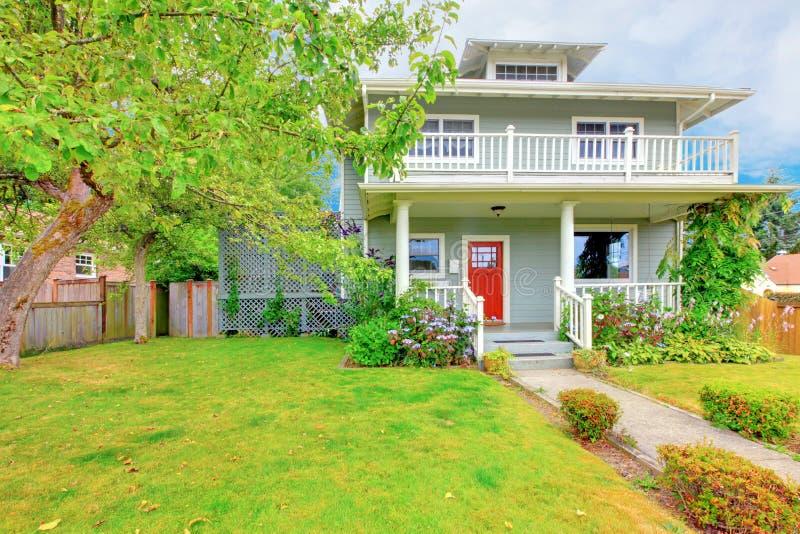 Casa de dos niveles verde americana exterior con el ajuste blanco y la puerta de entrada roja foto de archivo