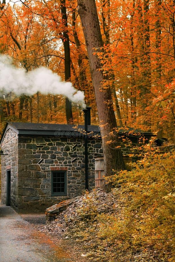 Casa de fumo da chaminé na paisagem da floresta com pouca casa na floresta do outono imagens de stock