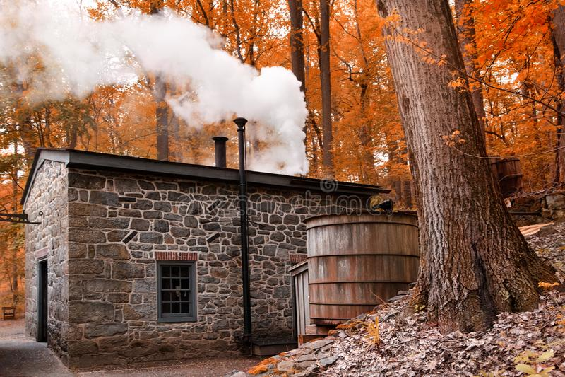 Casa de fumo da chaminé na paisagem da floresta com pouca casa na floresta do outono imagem de stock royalty free