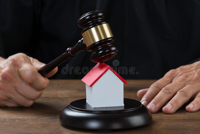 Casa de Holding Gavel On do juiz na mesa fotografia de stock royalty free