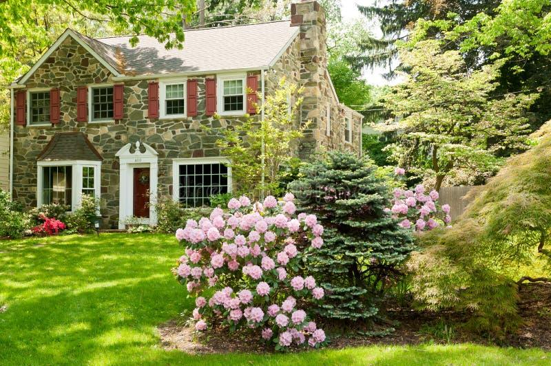 Casa de la familia con el césped delantero hermoso en resorte fotos de archivo