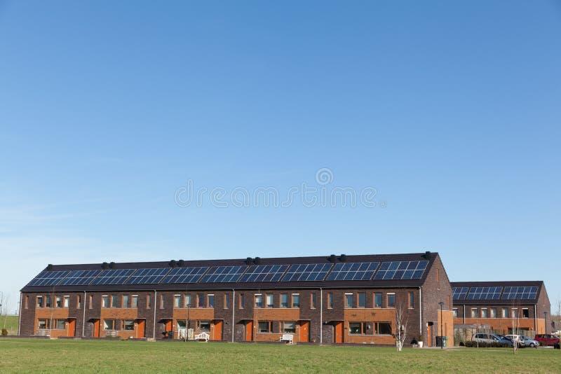 Casa de la familia con los paneles solares fotos de archivo