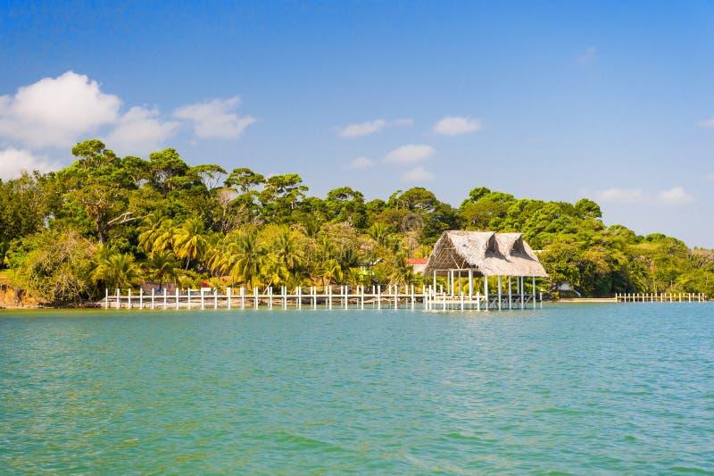 Casa de la madera y de la hierba en la playa tropical en Guatemala, tomas del santo Choza en orilla de mar en el cielo azul solea imagen de archivo libre de regalías