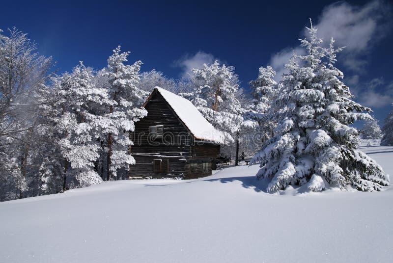 Casa de la montaña en nieve imagen de archivo