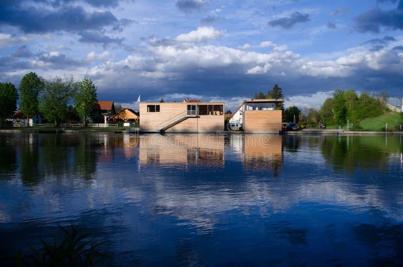 Casa de la orilla del lago con el cielo hermoso dramático fotografía de archivo