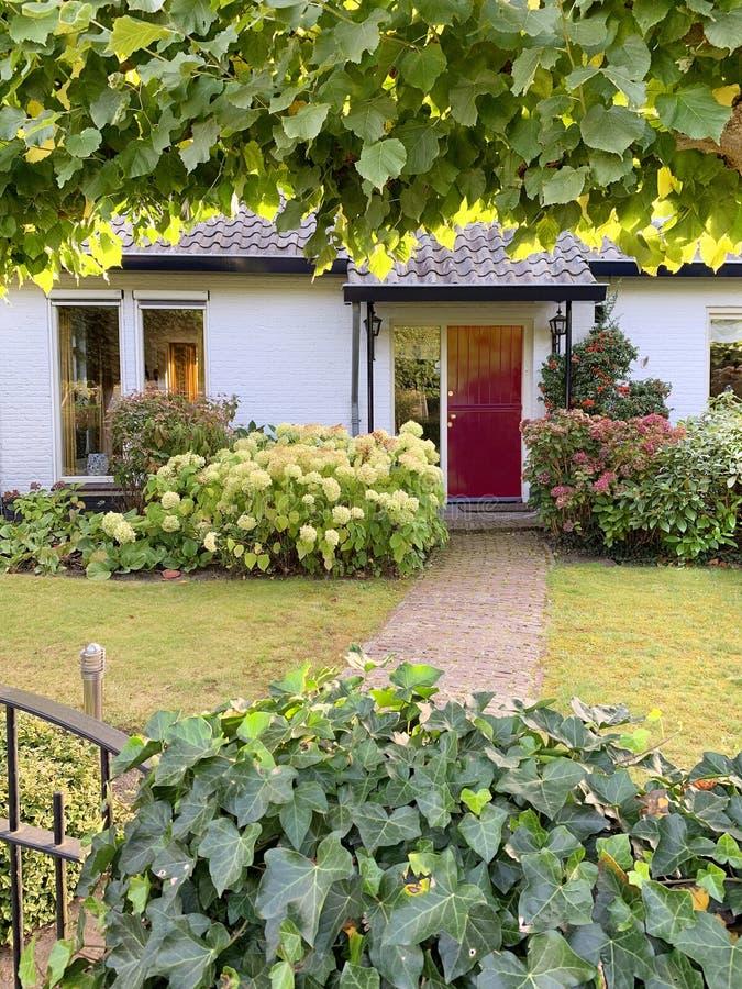 Casa de ladrillo y jardín holandeses fotografía de archivo