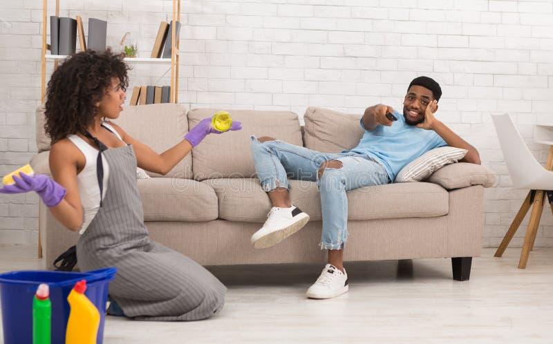 Casa de limpeza da mulher quando seu noivo que descansa no sofá foto de stock