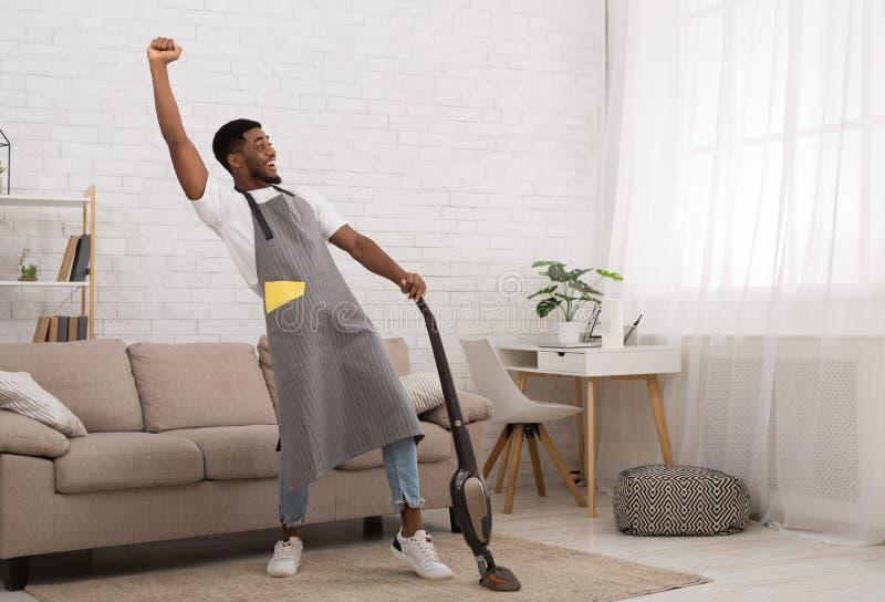 Casa de limpeza do homem negro com o aspirador de p30 sem fio imagens de stock royalty free