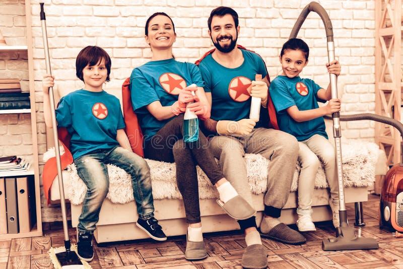 Casa de limpeza de sorriso da família do super-herói com crianças foto de stock