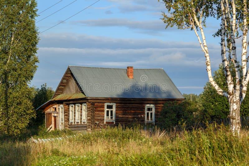 Casa de log velha com um pátio coberto de vegetação com a grama Vila de Visim, região de Sverdlovsk, Rússia imagens de stock royalty free