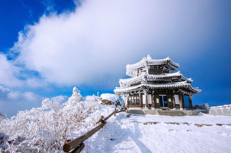 A casa de madeira é coberta pela neve no inverno, montanhas de Deogyusan foto de stock